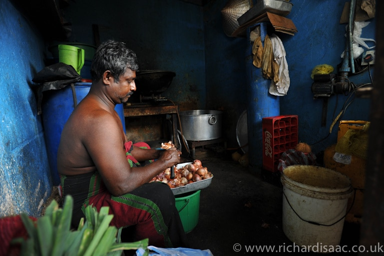 A man peeling vegetables in his roadside workspace - Colombo, Sri Lanka