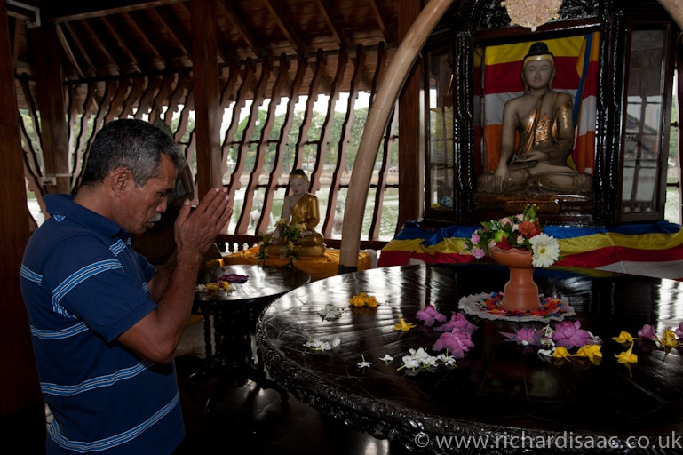 A man praying inside Seema Malaka Buddhist Temple - Colombo, Sri Lanka