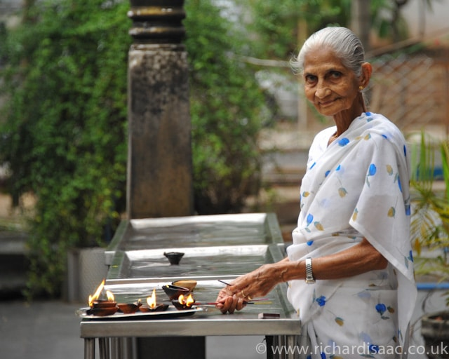 An old lady lighting incense burners at Gangaramaya Buddhist Temple - Colombo, Sri Lanka