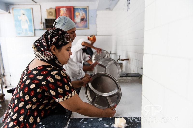 People clean their plates after eating at the Gurdwara Bangla Sahib Sikh Temple, Delhi - 12/11/12