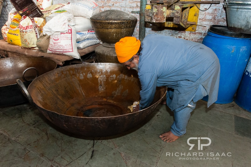 A chef cleans a huge cooking dish at the Langar, or kitchen area, of the Gurdwara Bangla Sahib Sikh Temple, Delhi - 12/11/12