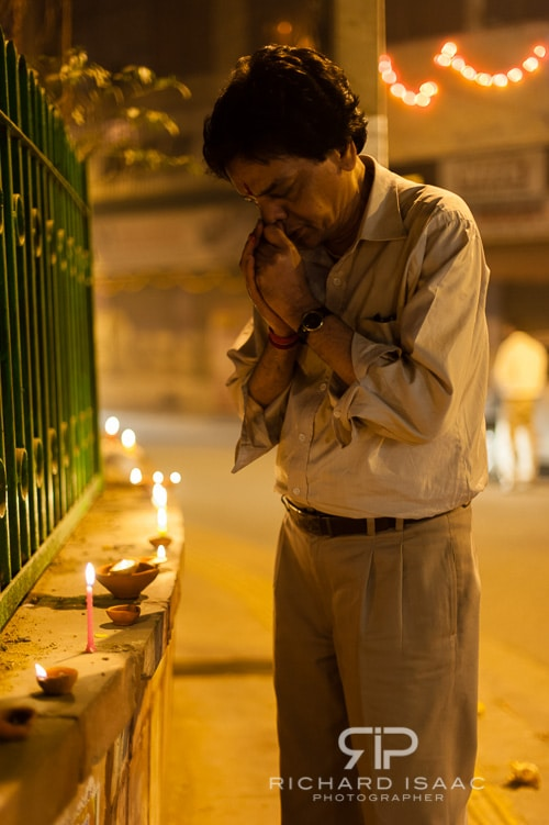 A Delhi resident lights a lamp and prays outside his home, on the first night of Diwali - 13/11/12