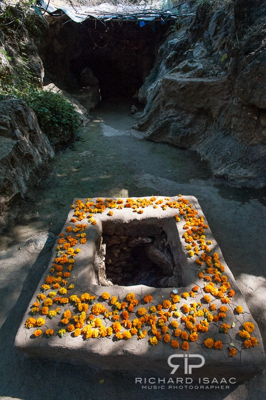 An underground spring sits in the foreground with flower petals laidd around the well, in the background is the entrance to a Hindu shrine (see below pic)