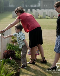 A mother and son place a rose on the grave of a relative who served as a member of the Commonwealth Armed Forces who lost their life serving in one of the World Wars