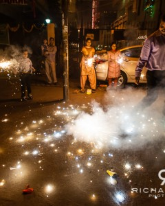 A Delhi family celebrate Diwali with fireworks in the street outside their home - India