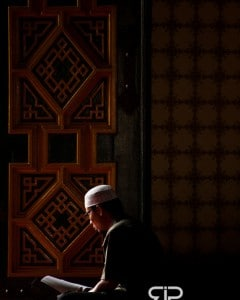 A muslim reads the Qu'ran inside The Great Mosque, Masjid Raya - Medan, Sumatra, Indonesia
